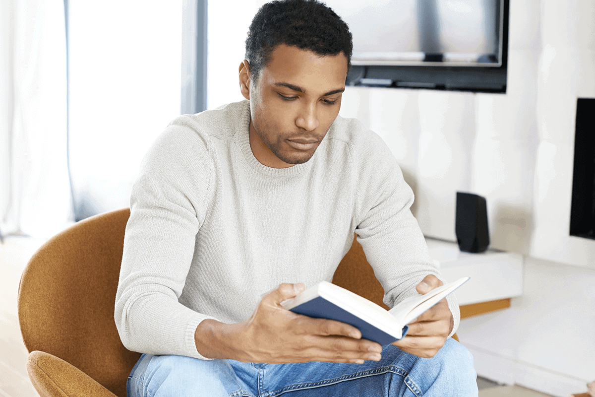 man reading a book sitting on a couch