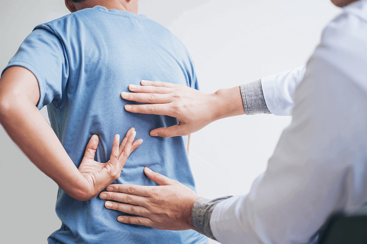 doctor examining a man's middle and lower back
