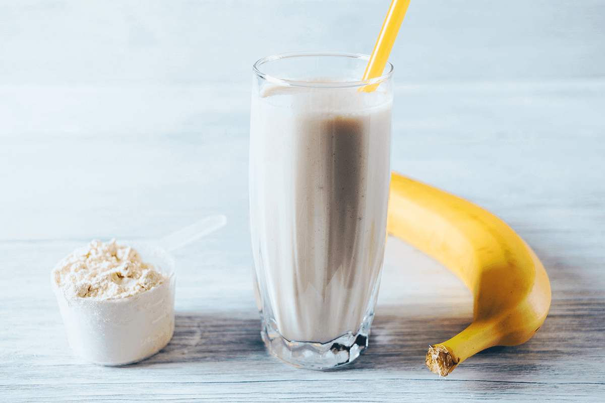 calcium powder next to a glass of milkshake with yellow straw and a banana