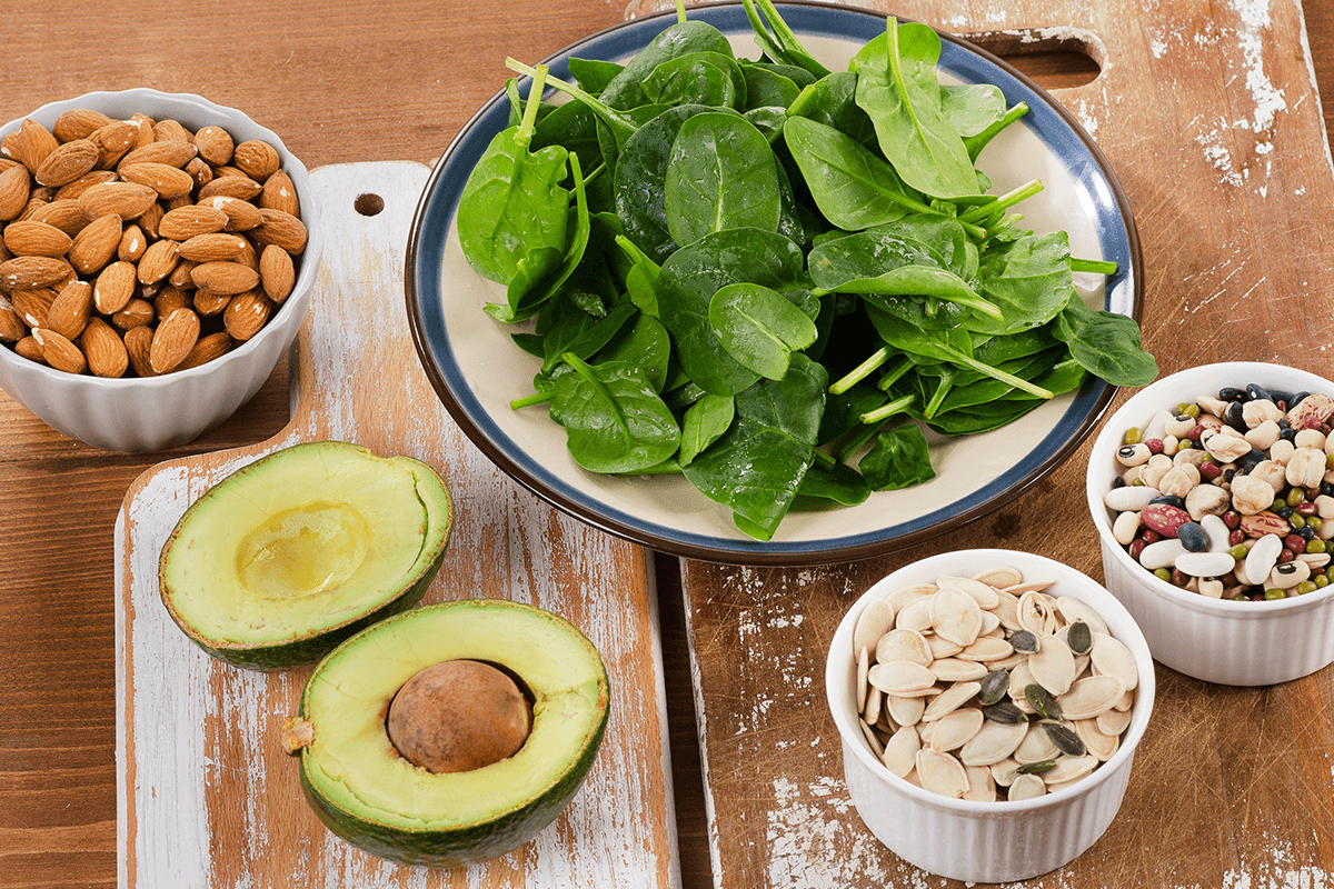 nuts, beans, avocados, spinach in bowls and on plates