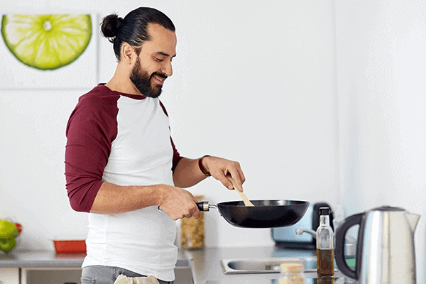 man holding a pan and wooden spoon, cooking in kitchen