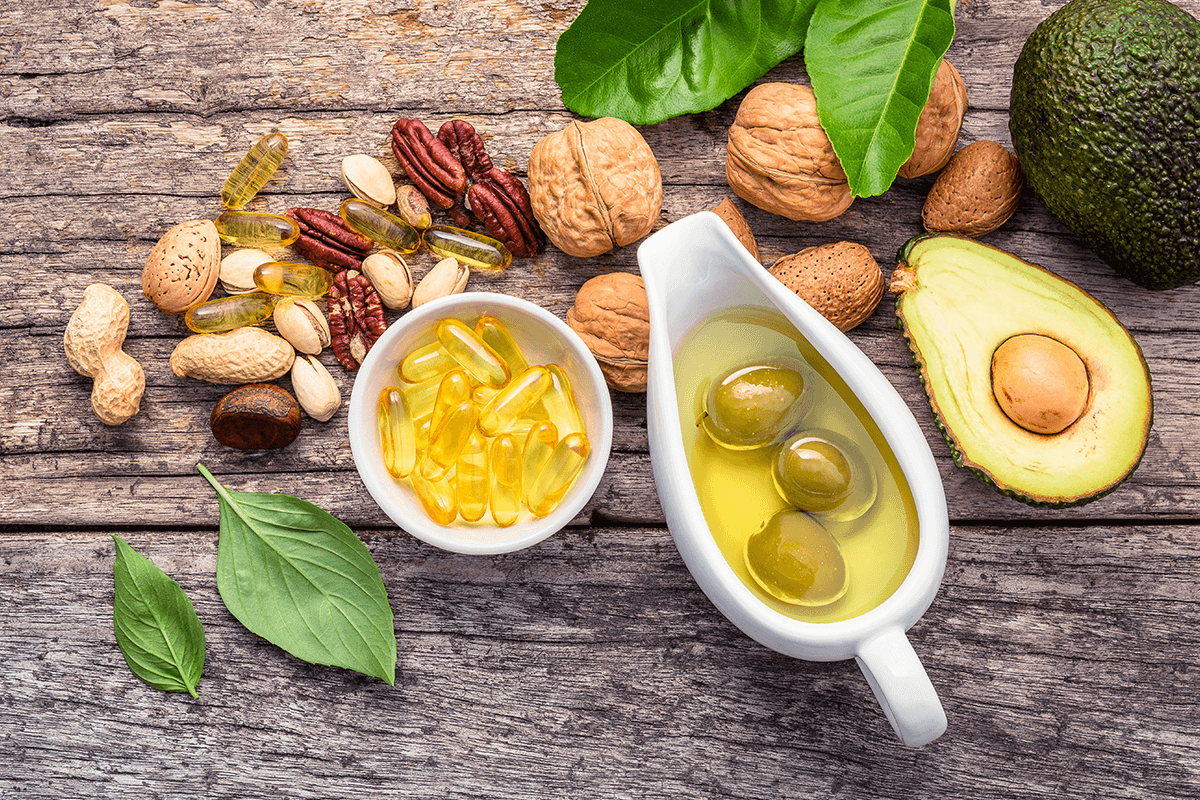 variety of nuts, avocados, olive oil with olives in a white jar and fish oil supplements in a white dish on a wooden table