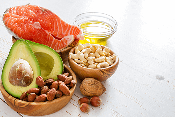 clear glass filled with oil, wooden bowl filled with cashews, wooden bowl filled with almonds and a cut up avocado, and wooden bowl filled with a piece of meat
