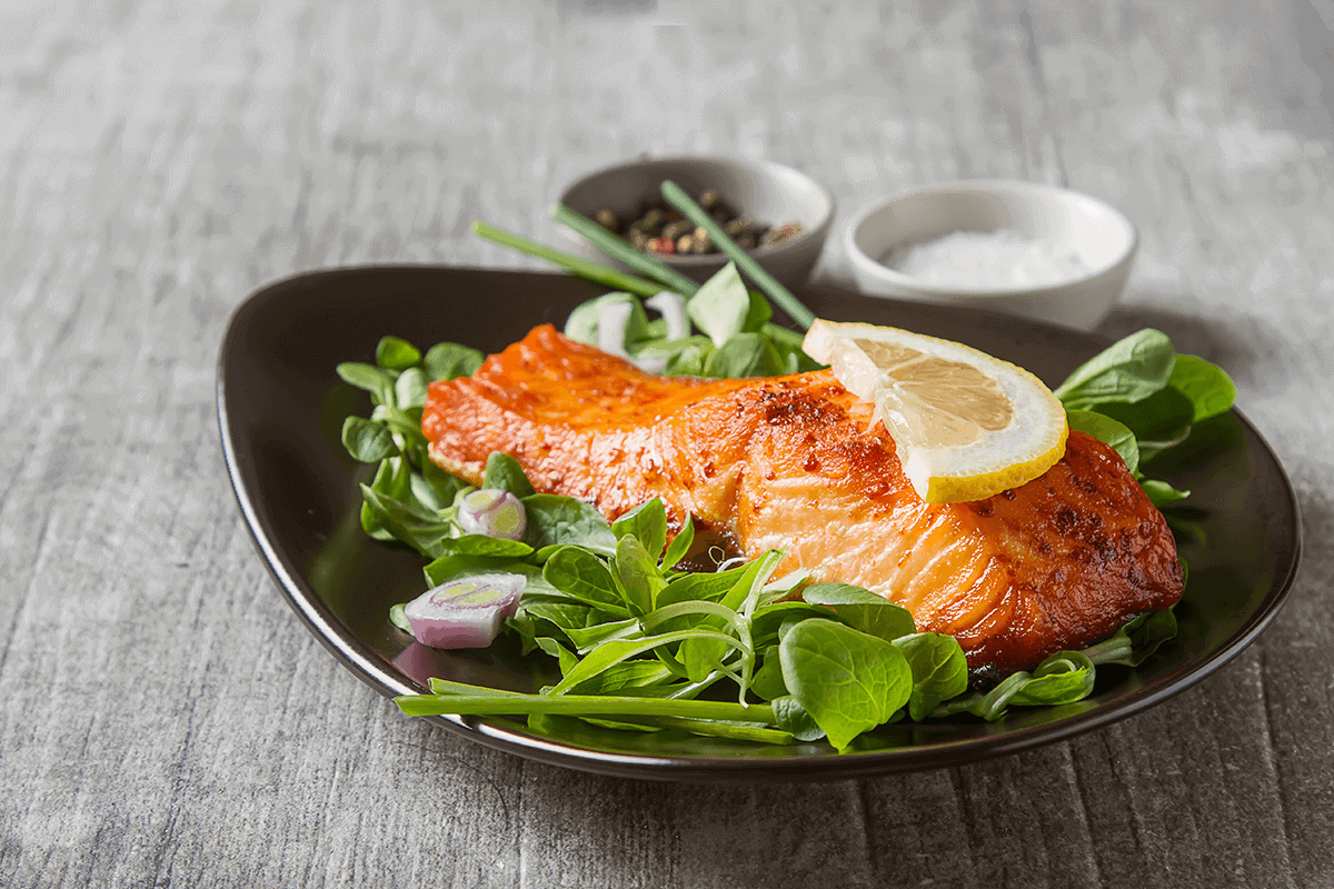 salmon with lemon slice on top of greens on black dish