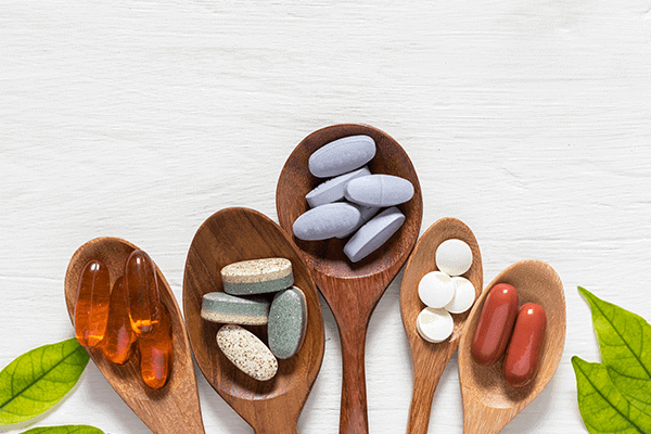 five wooden spoons with softgel, tablet, and capsule supplements