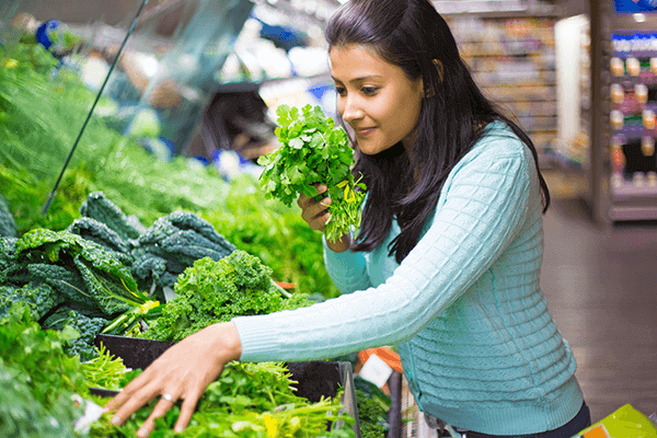 woman in the leafy greens aisle in grocery store picking up and smelling parsley