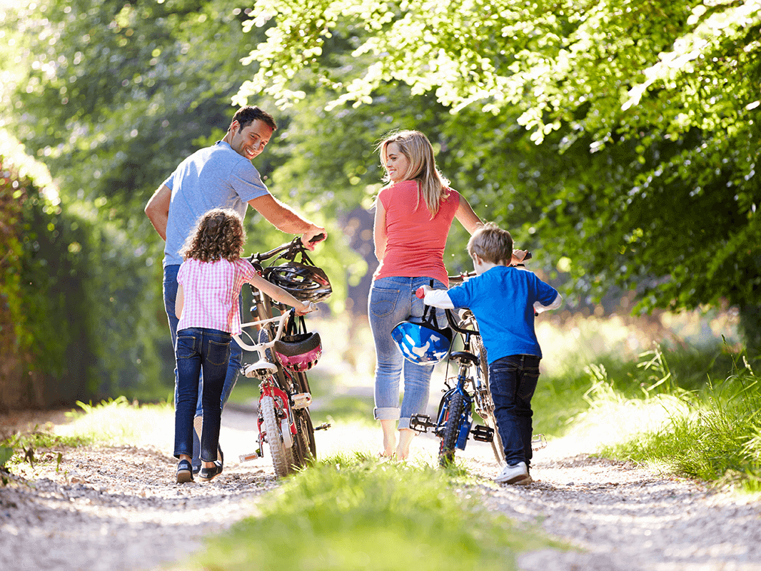 family of four pushing their bikes outside in a forest area