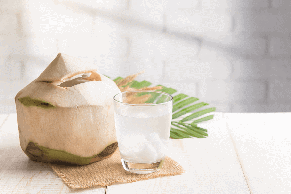 raw coconut cut up next to a glass of coconut water