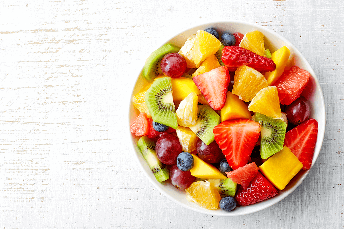a bowl of a variety of cut up fruits