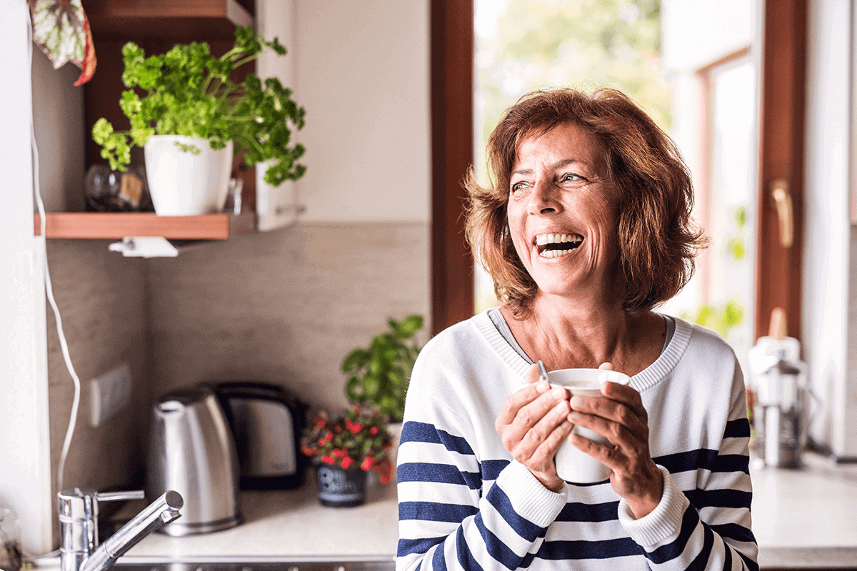 woman in a kitchen holding a jug and laughing