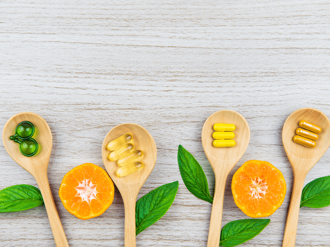 four spoons with leafs and cut up orange slices with vitamins on the spoons
