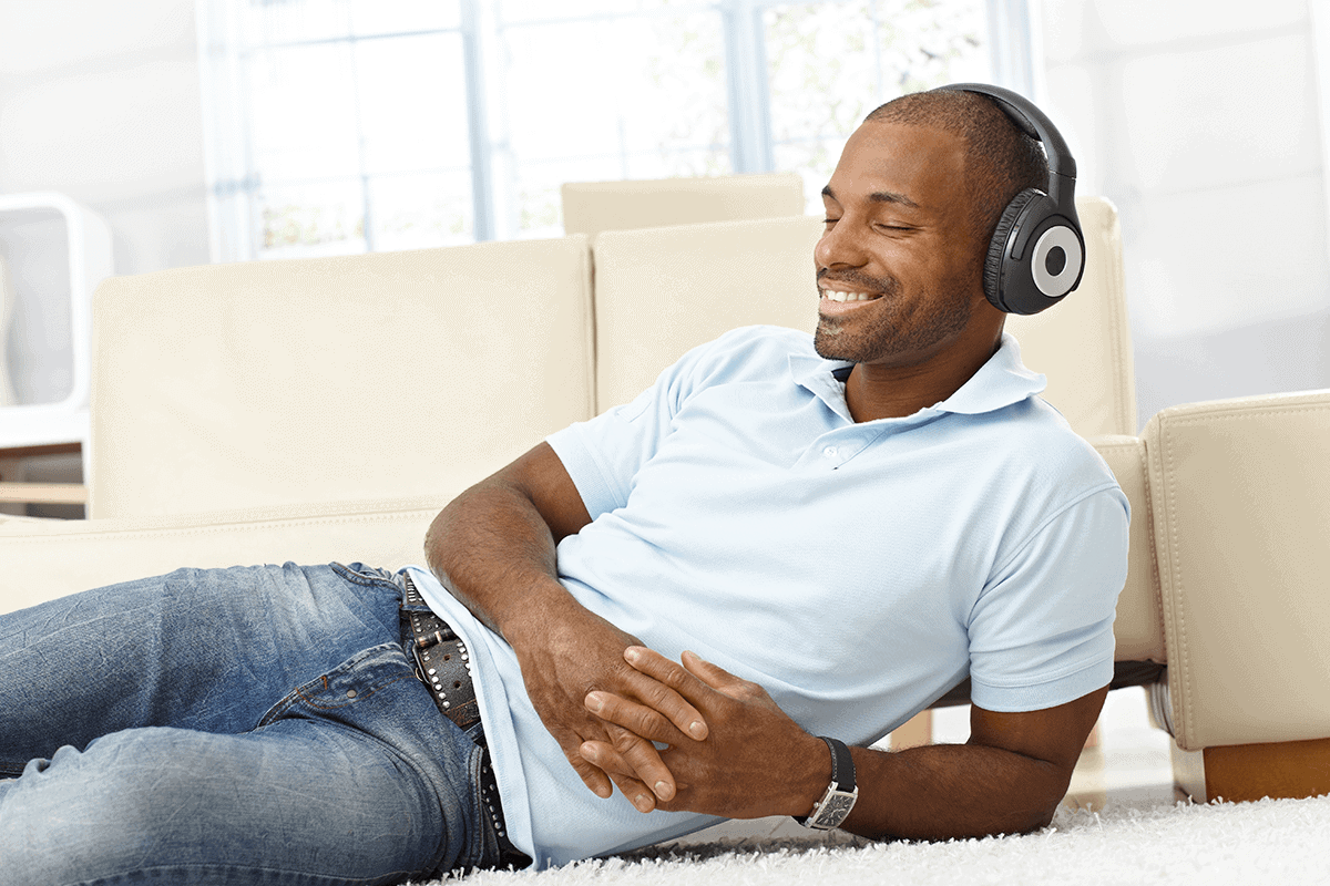 Man laying with headphones on smiling
