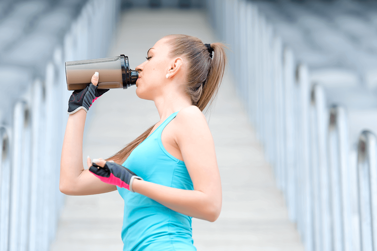 woman in active wear drinking protein from plastic bottle