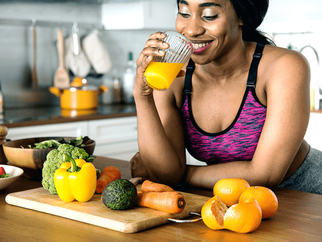 woman leaning on kitchen table drinking orange juice with raw fresh fruits and vegetables around her