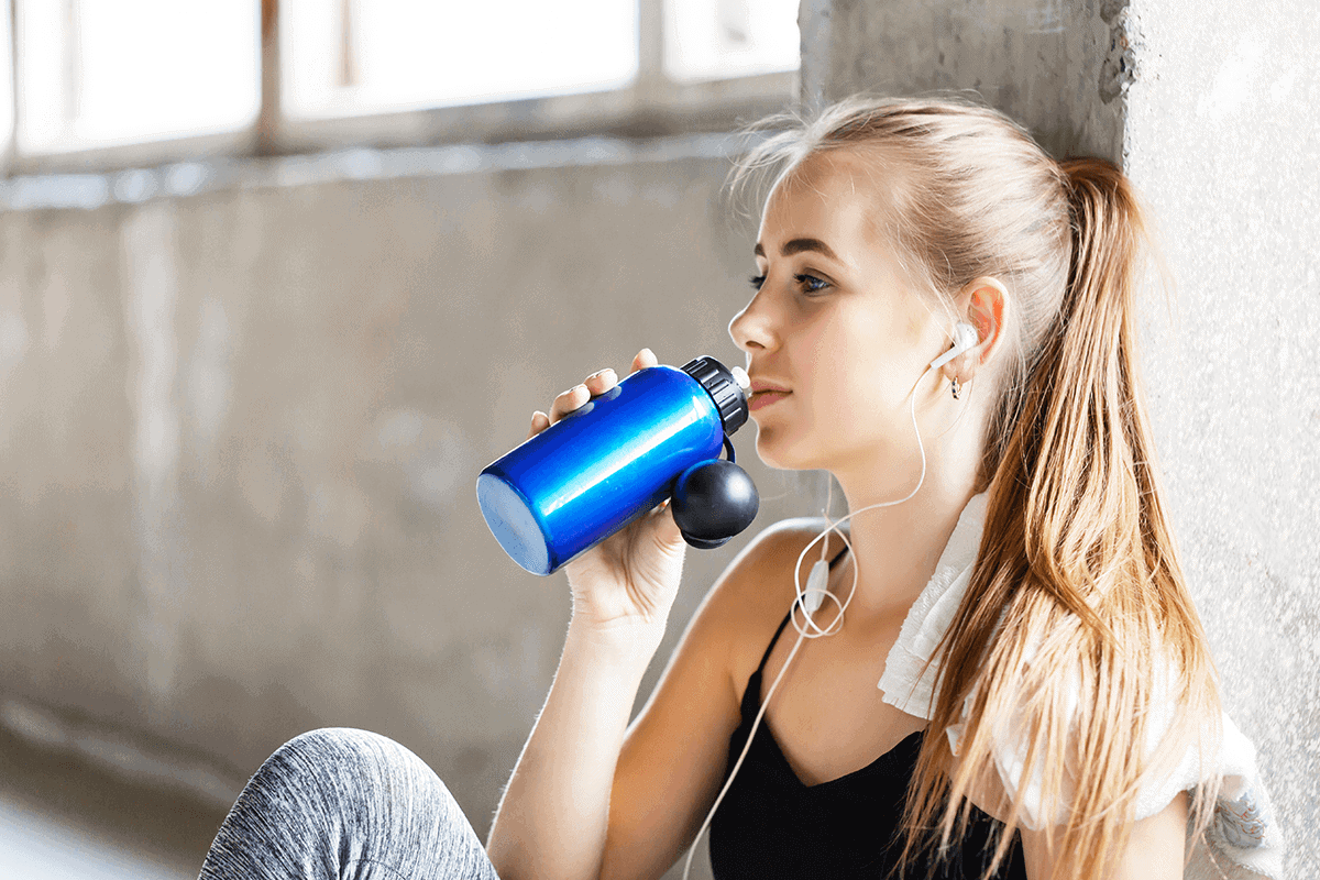 woman sitting in active wear and drinking from a blue water bottle