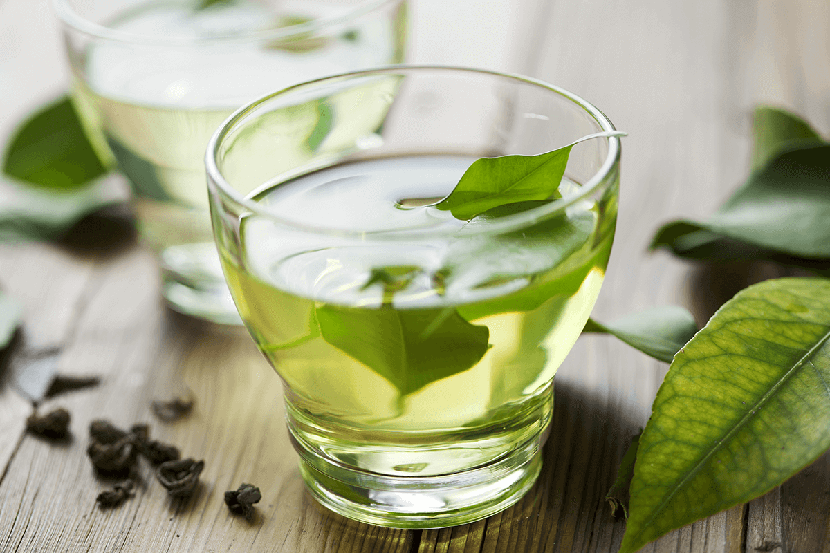 Green tea in clear glass with green tea leaves on wooden table