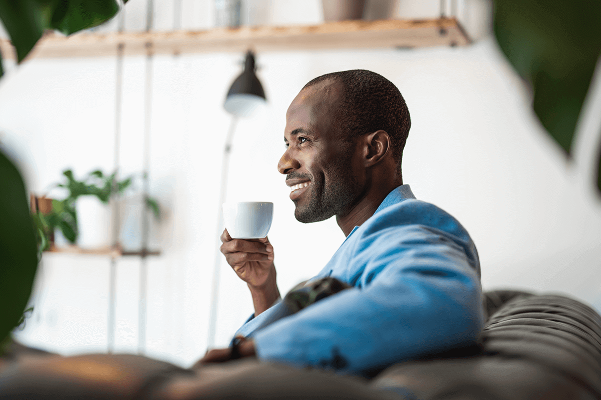 man sitting on couch smiling and drinking from white cup