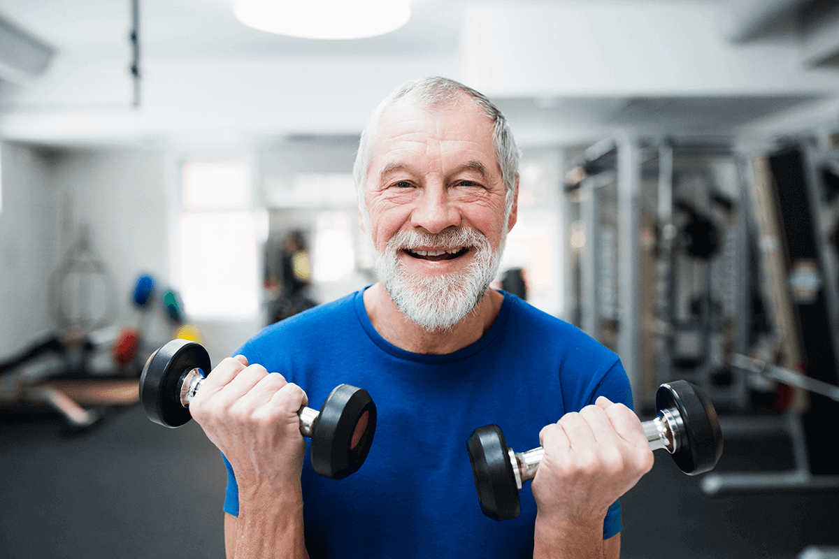 older man lifting dumbbells at gym smiling into the camera