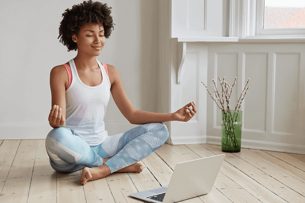 woman sitting on floor, meditation in front of open laptop