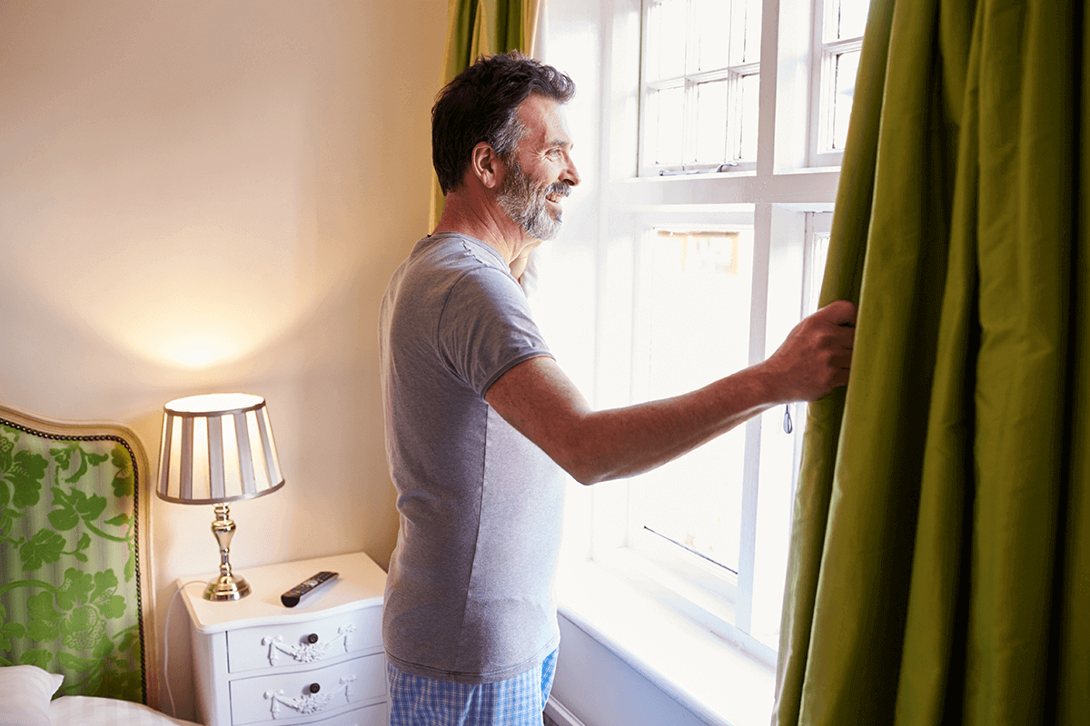 man looking out his bedroom window in pjs looking at the sunrise