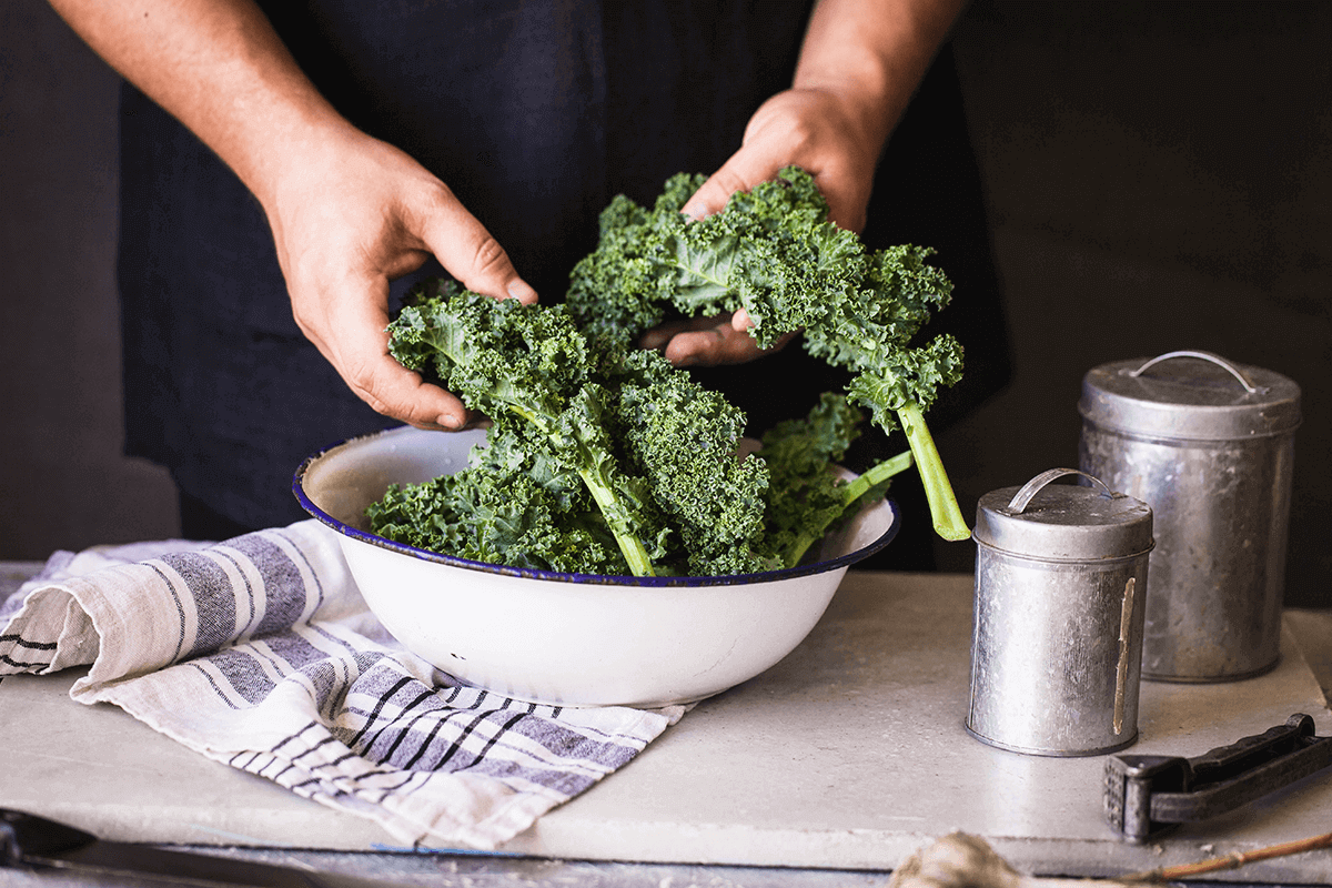 close up of person's hands holding kale over a large bowl