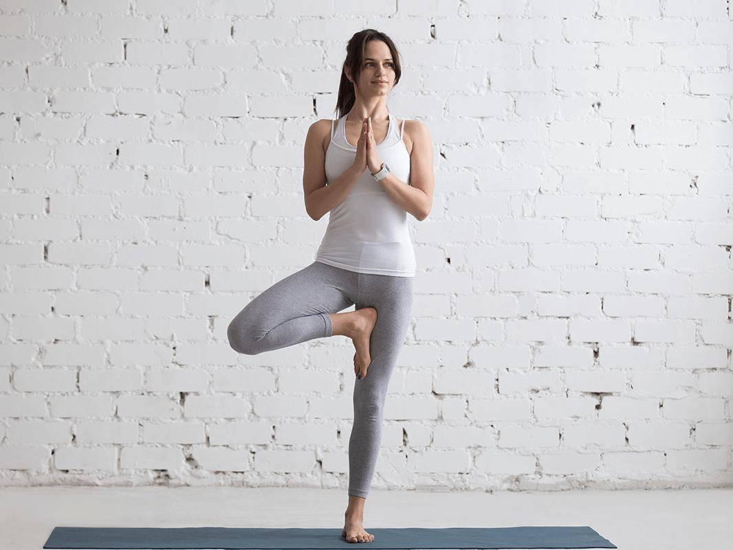 woman doing a yoga pose standing on one leg and balancing