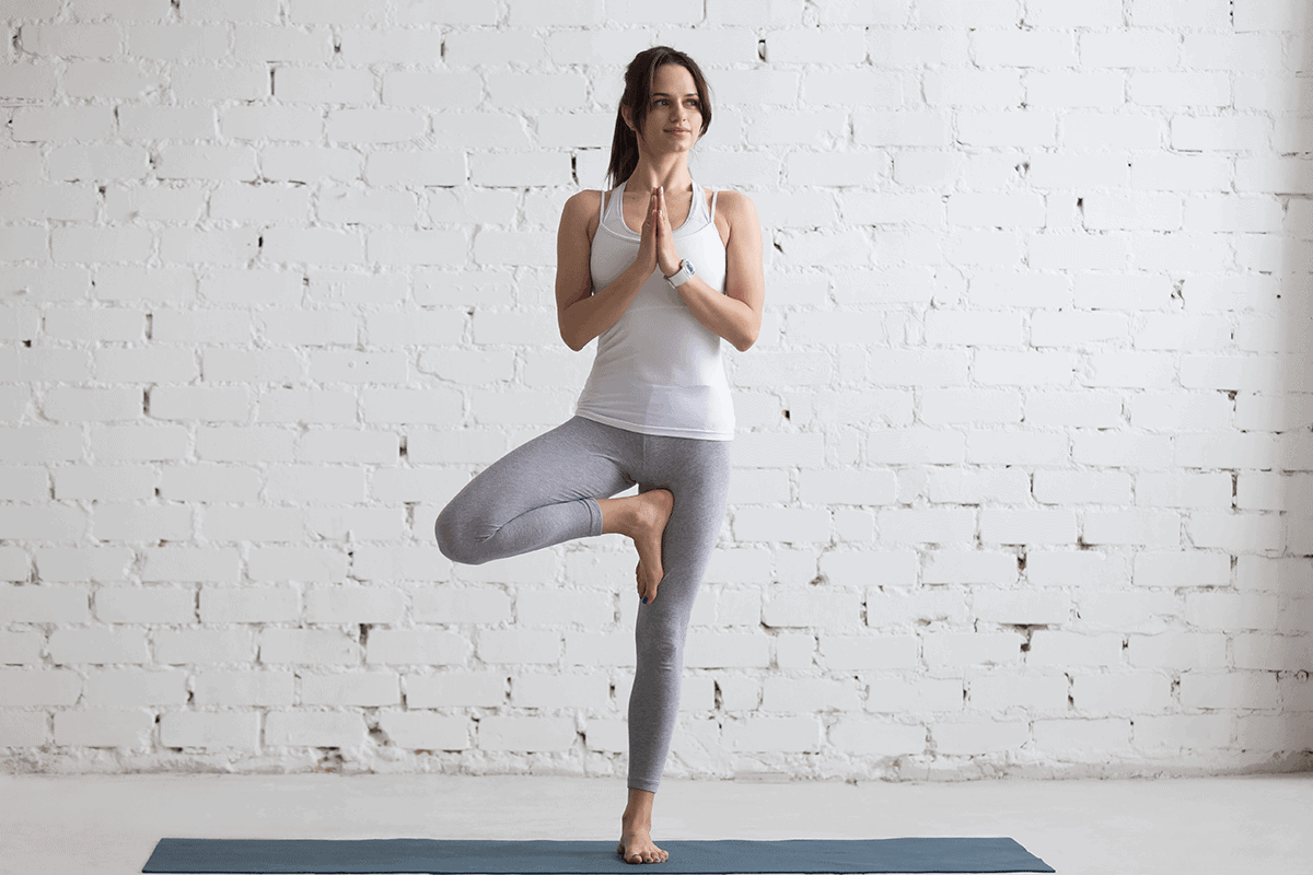 woman doing a yoga pose standing on one leg and balancing