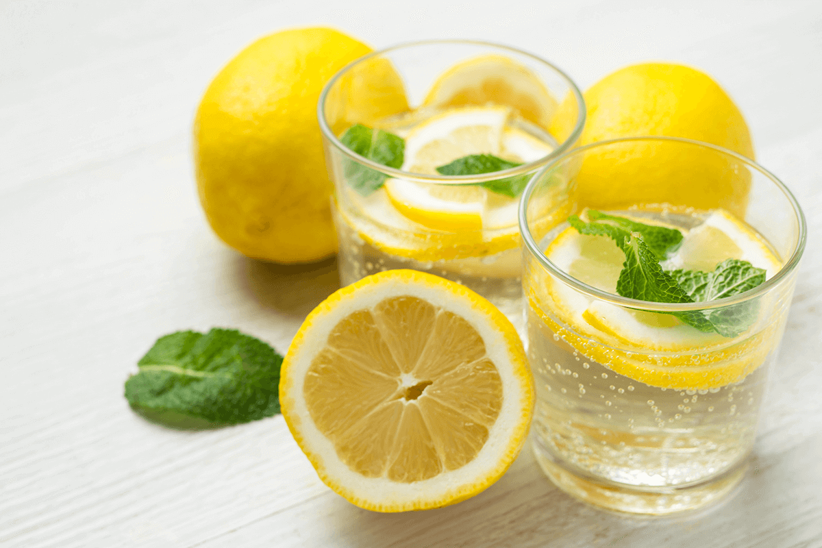 two glasses of water with cut up lemons and whole lemons next to them