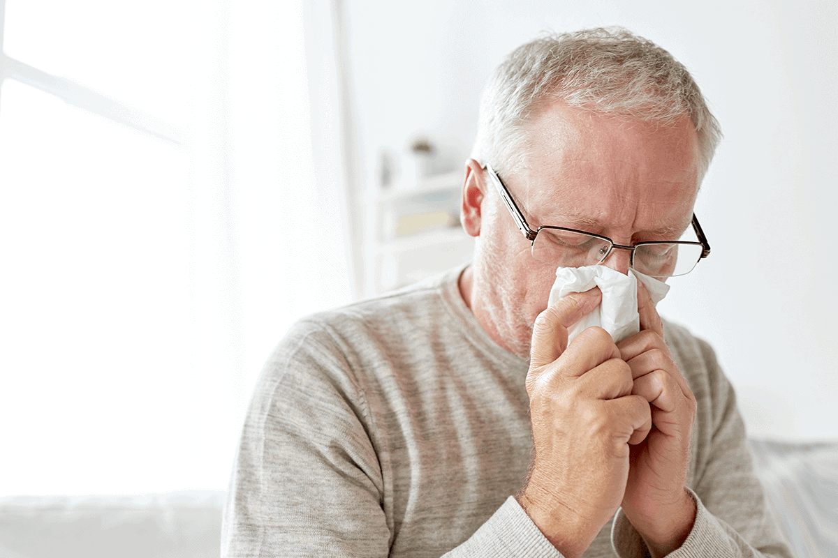 man blowing his nose into a tissue