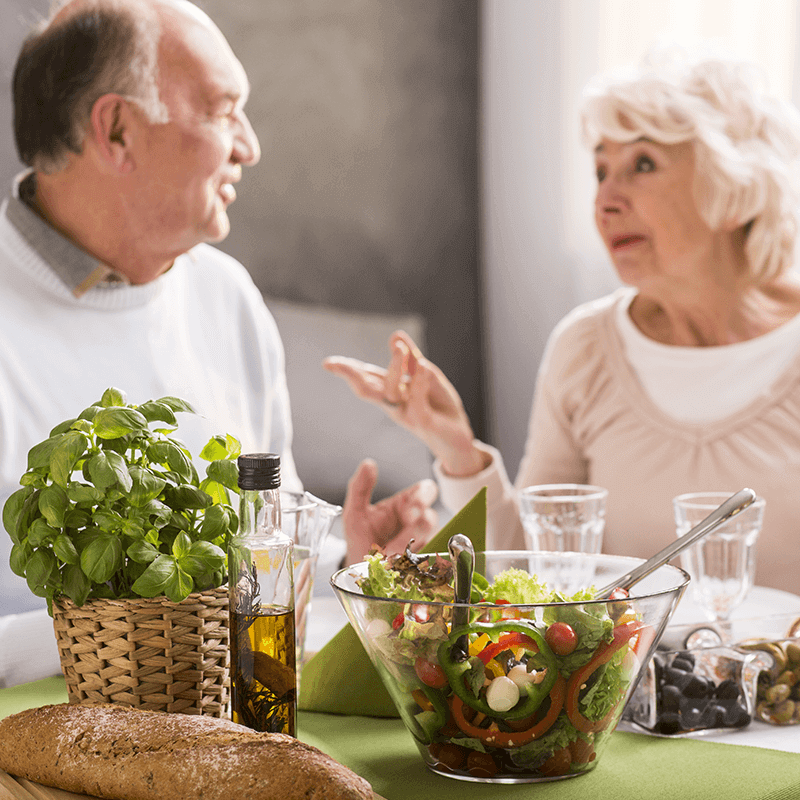 a man and a woman talking over salad