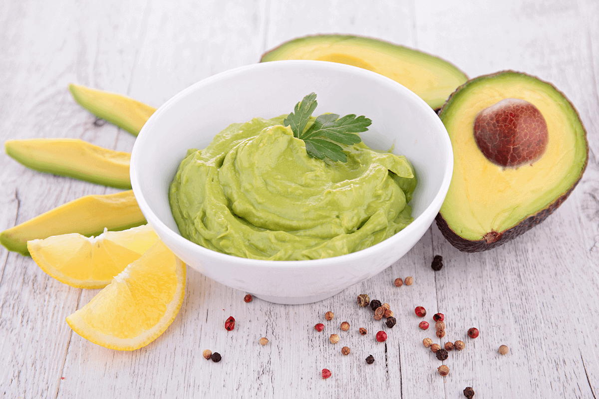 A bowl of guacamole surrounded by avocado and lemon