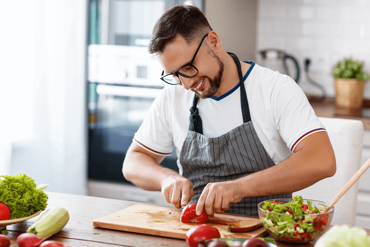 Man wearing a chef apron slicing a tomato on a cutting board for his salad