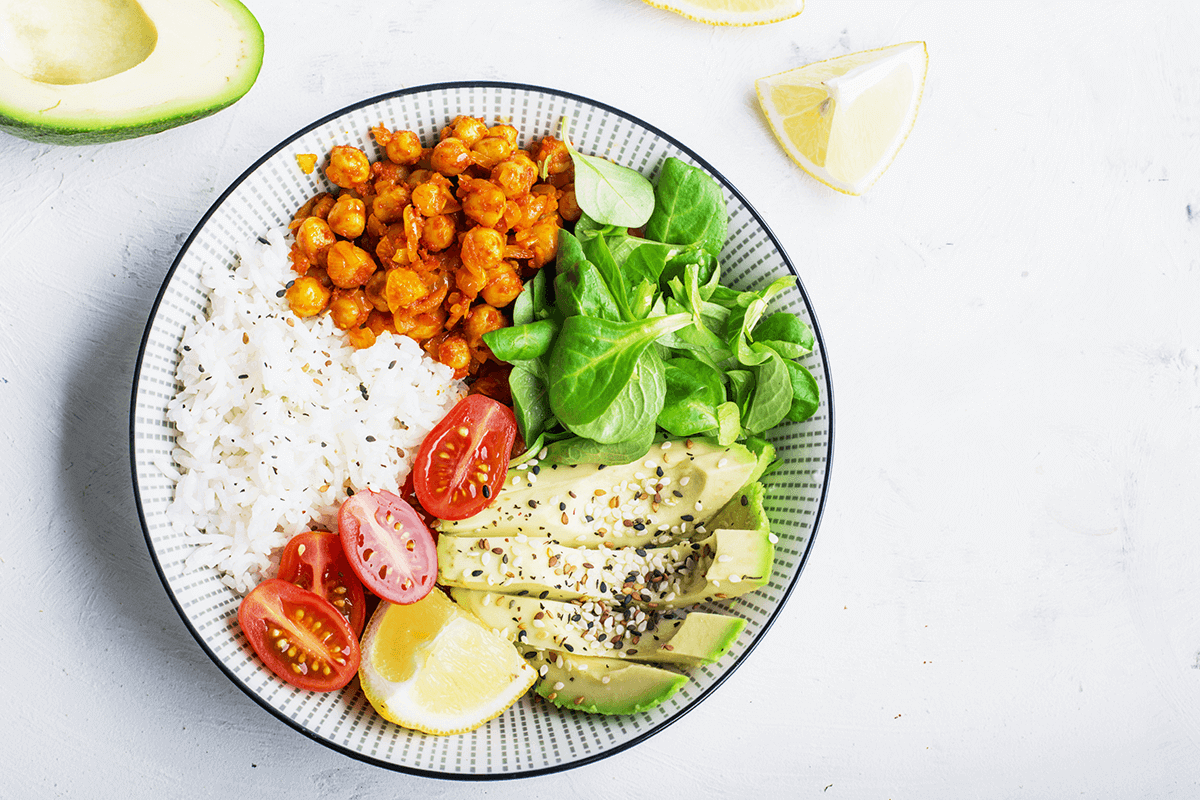 A bowl of healthy foods including rice, chickpeas, cherry tomatoes, lemon, avocado, and spinach.