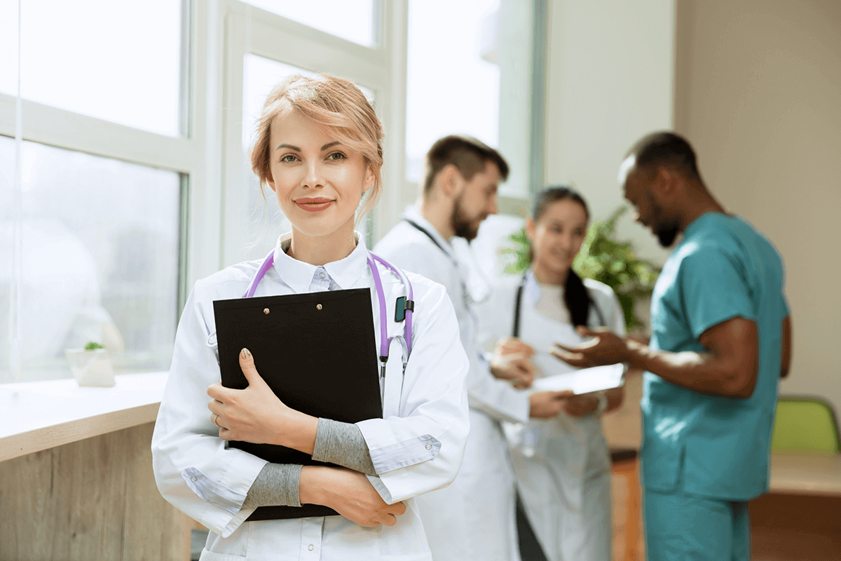 medical doctor with clipboard standing with staff behind her