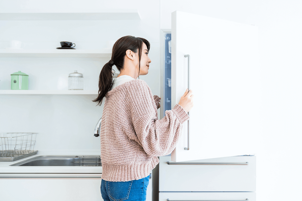 woman opening her refrigerator and looking inside
