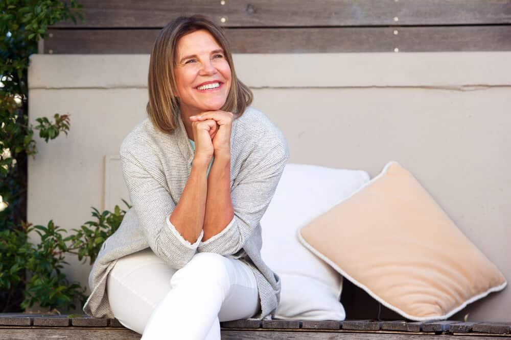 Healthy, smiling woman sitting on bench