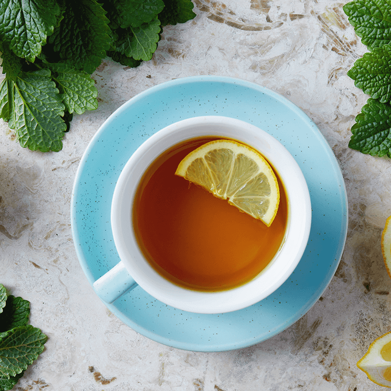 A blue tea cup full of lemon tea with slices of lemon next to it.