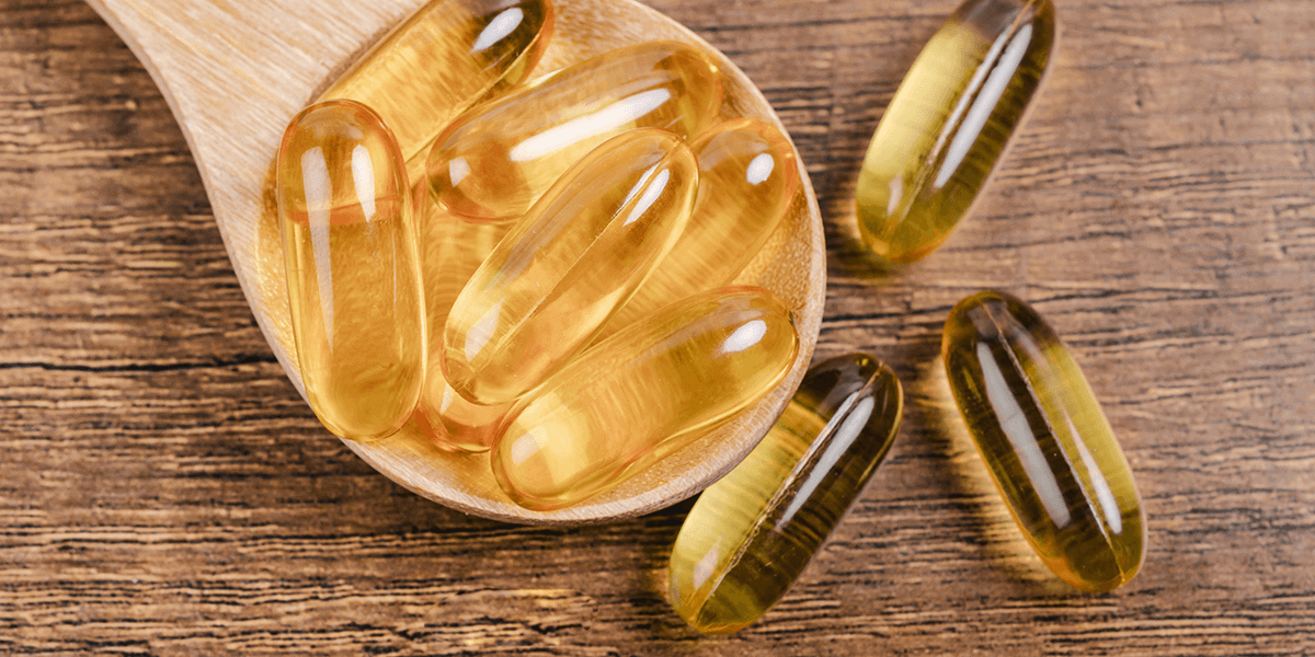 fish oil supplements on a wooden spoon