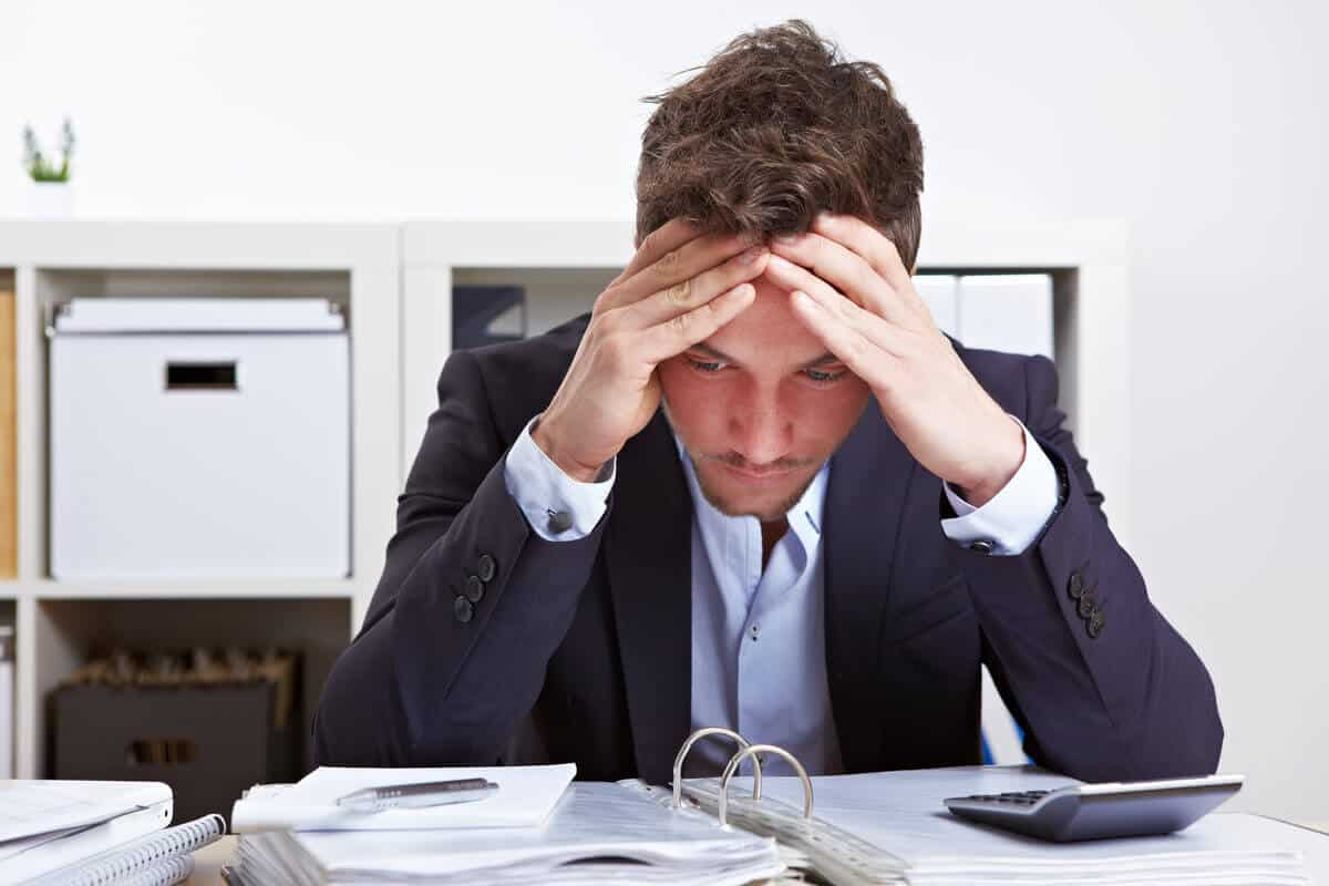 Man sitting at a desk holding his head, stressed