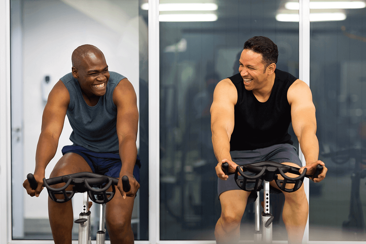two men cycling in the gym
