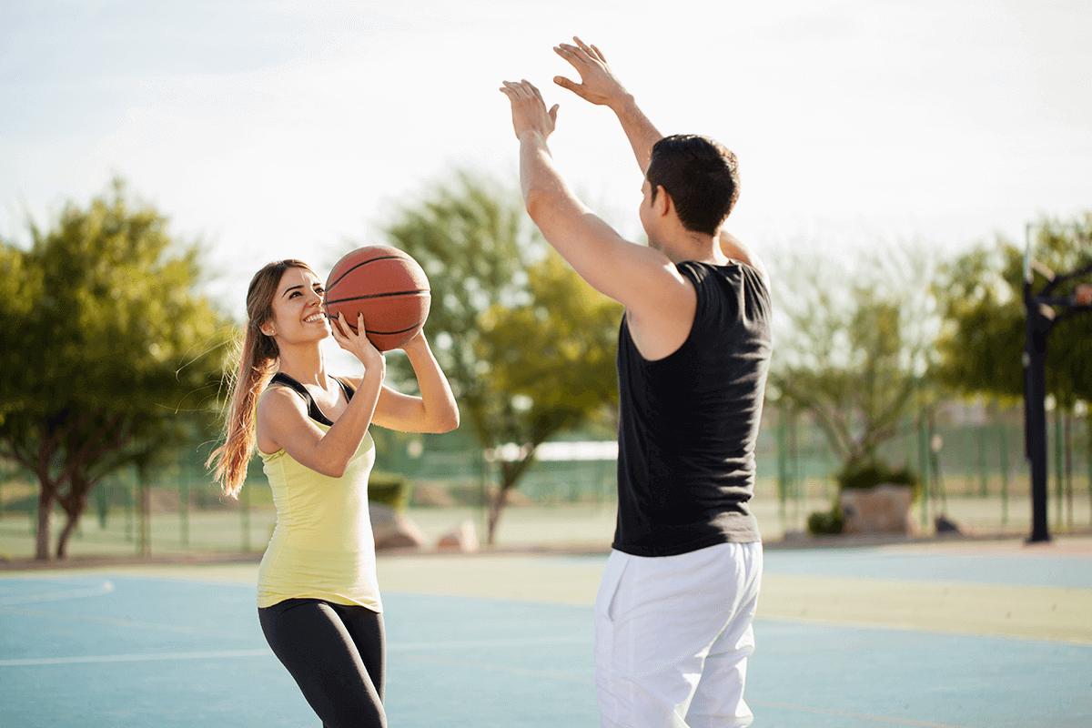 woman and man playing basketball outdoors