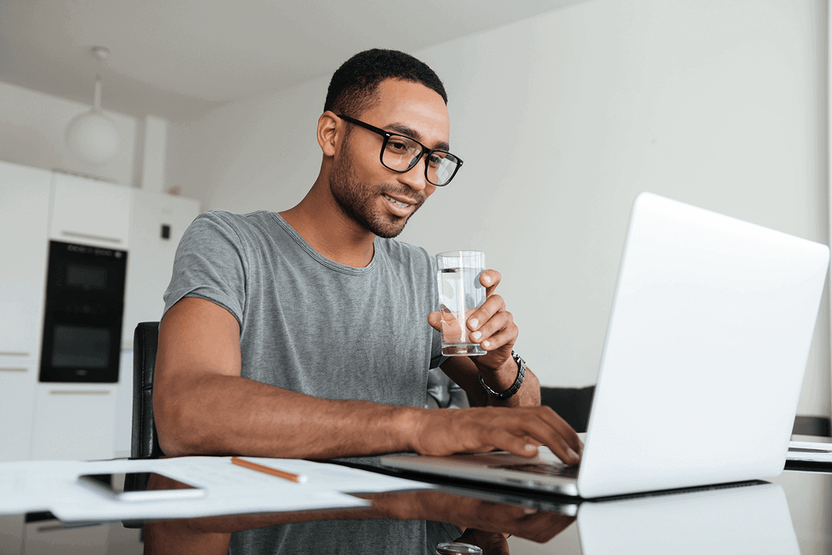 man on his laptop drinking water from a glass