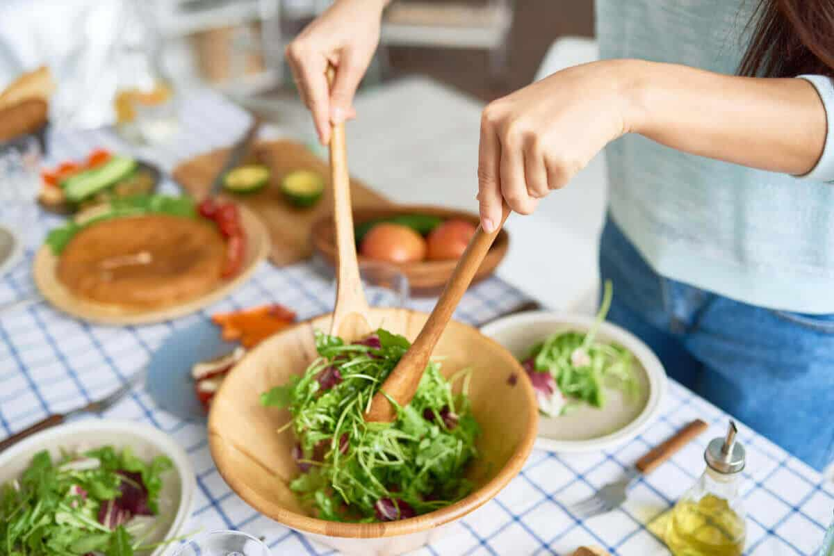 woman making a salad in brown bowl