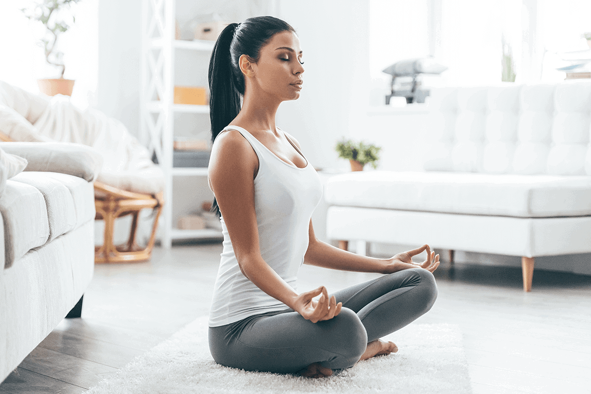 woman sitting cross-legged meditating at home