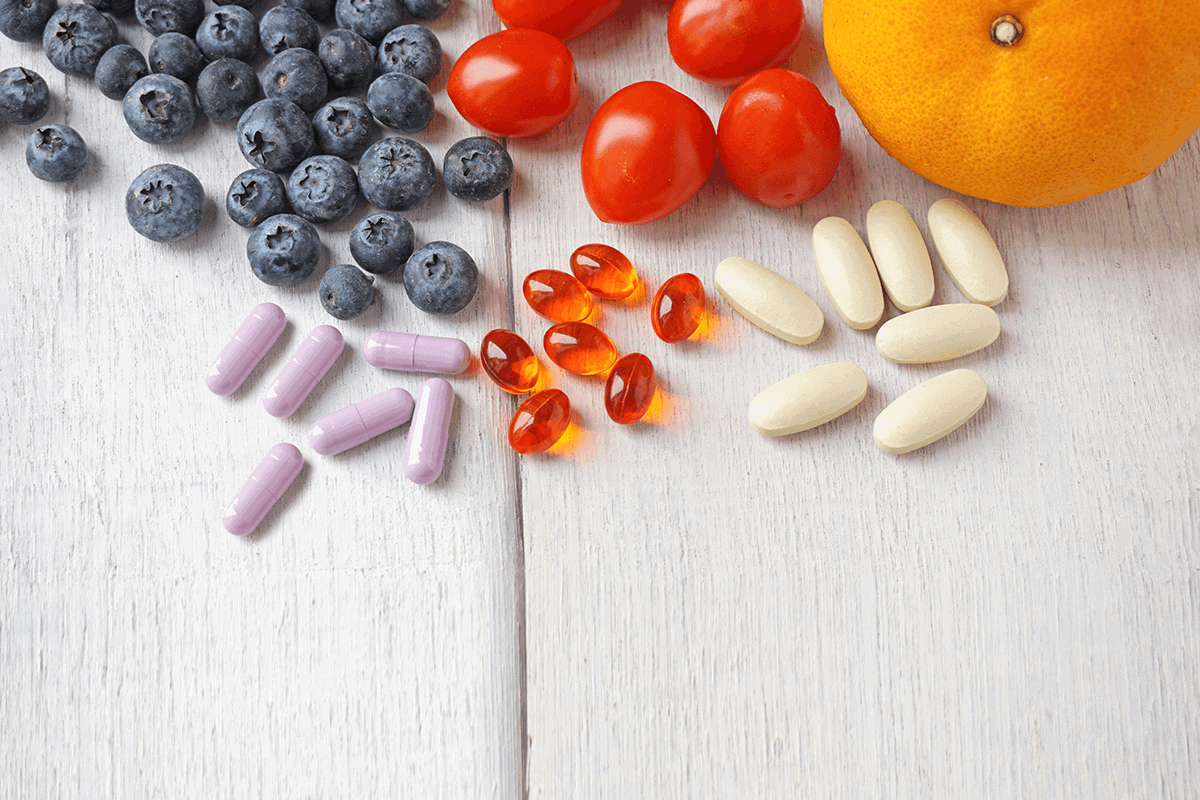 orange, tomatoes, and blueberries next to supplement capsules, and softgels