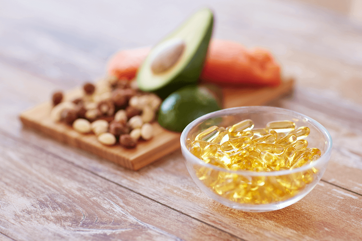 fish oil supplements in a clear bowl next to nuts, avocados, and fish on a board