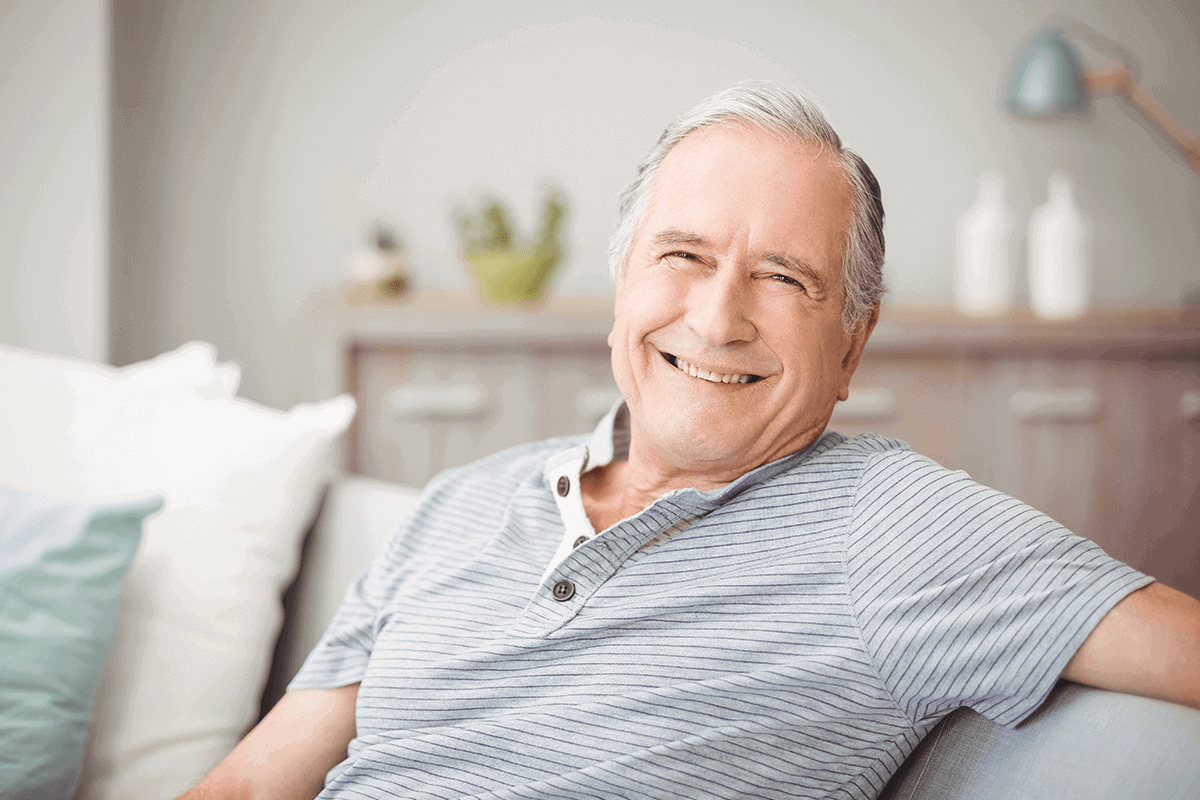man smiling sitting on couch in living room