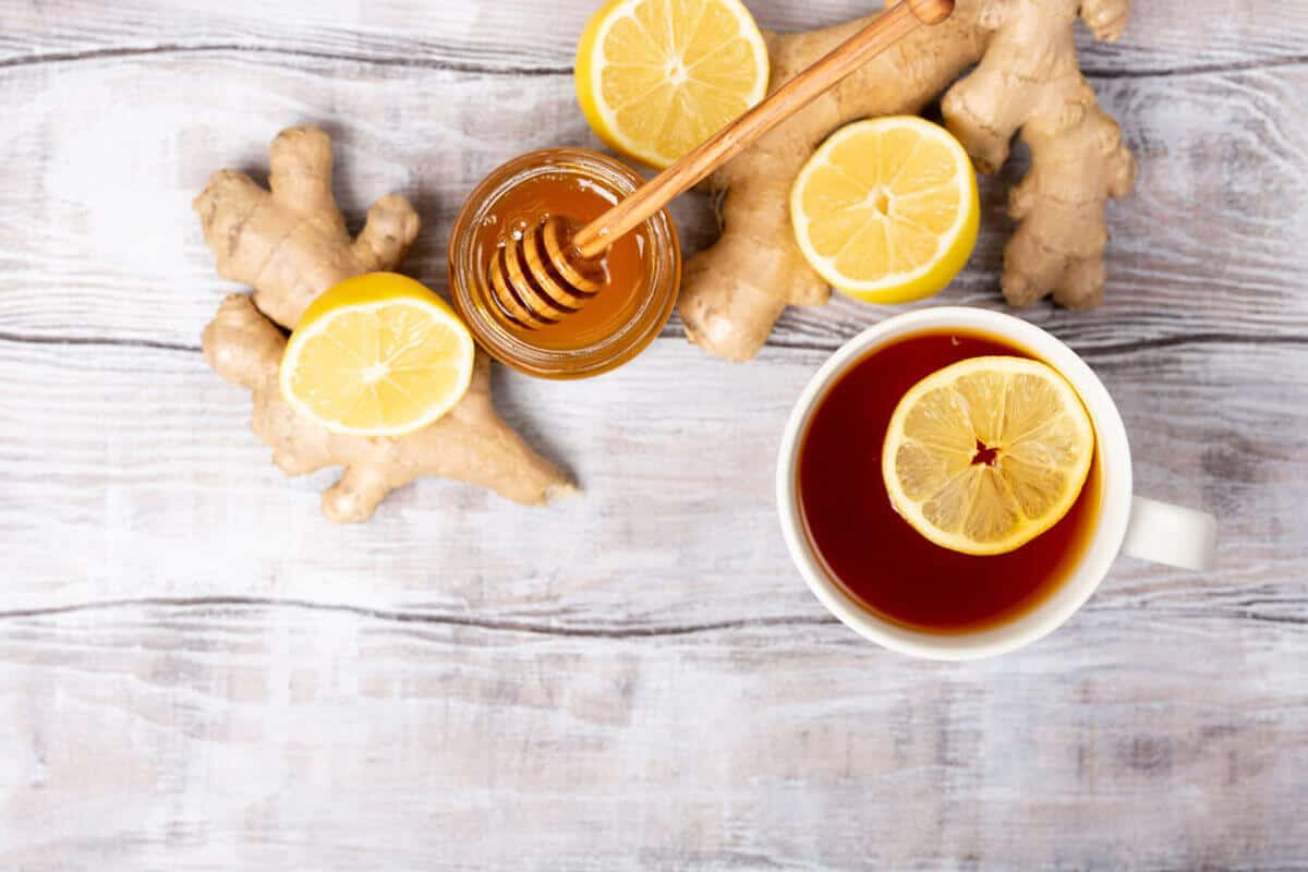 Cup of Ginger tea with lemon and honey on a dark blue background, top view