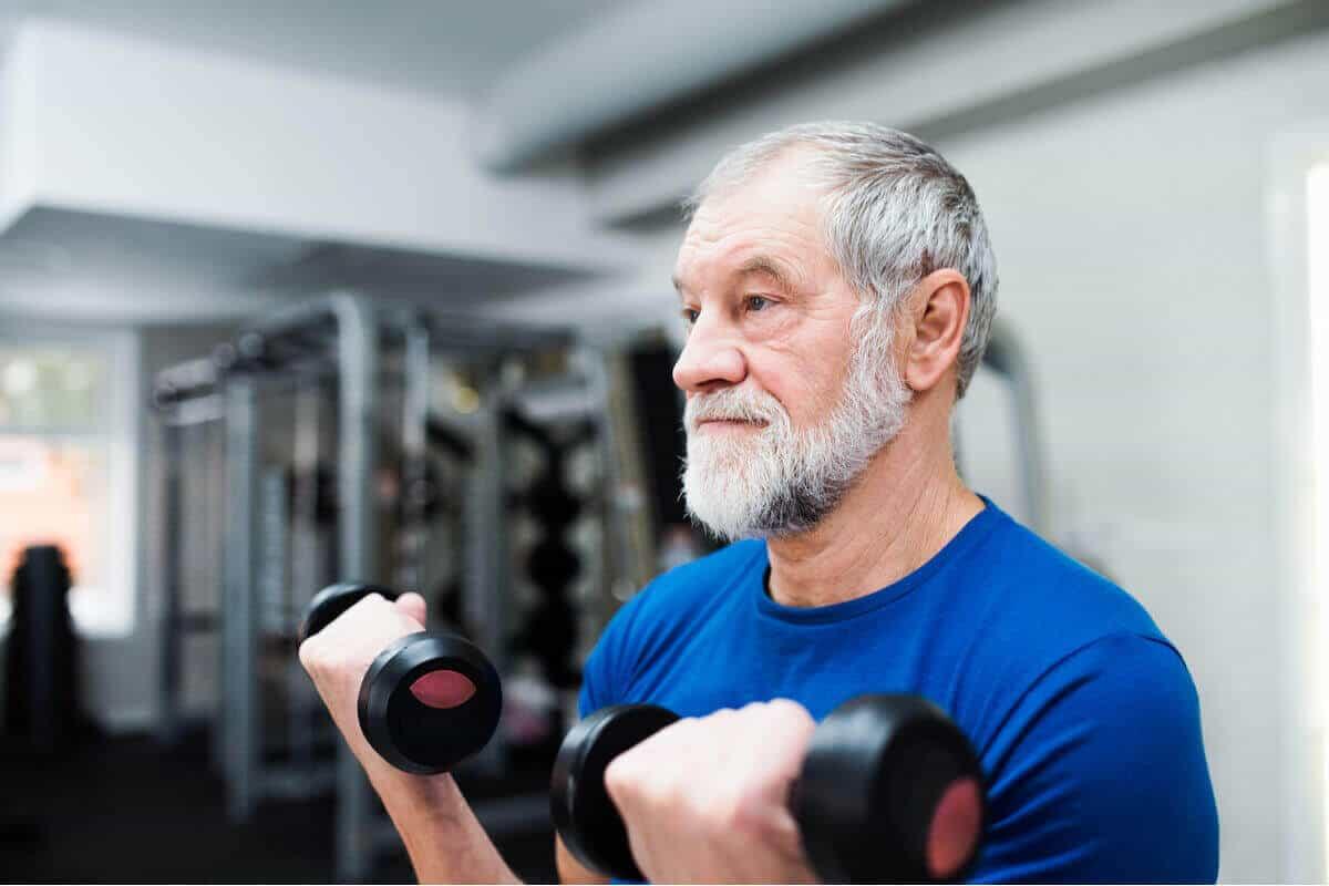 older man lifting dumbbells at the gym