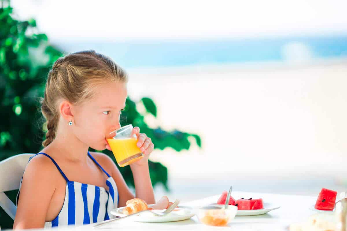 child drinking orange juice while on vacation